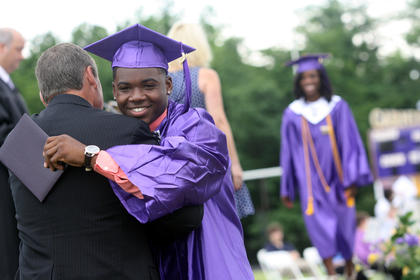 Deantuane Yocum hugs Bardstown City Schools Superintendent Brent Holsclaw after he receives his diploma during graduation Saturday.
