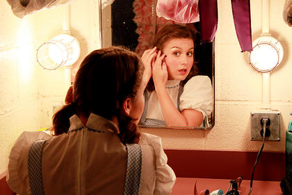 """Trish Epperson, who portrays Dorothy Gale in """"The Wizard of Oz,"""" gets ready before a dress rehearsal Wednesday night. The musical premiered on the J. Dan Talbott Amphitheatre stage Thursday to a record crowd of 1,006 for an opening of a second musical."""
