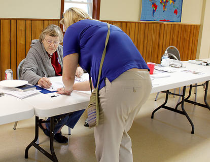 Poll worker Mary Conley signs in a voter during Tuesday's general election. Conley was working at the Wickland Baptist Church location.