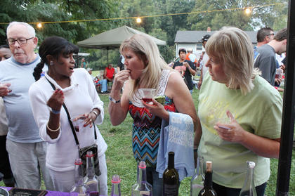Maggie Miles, left, and Barbara Thompson react as Polly Hall eats a muscadine while trying some homemade wine. Bob Johnson's muscadine wine was the winner.