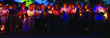 Hundreds of community members attended a candlelight vigil Monday night in honor of slain Bardstown Police Officer Jason Ellis, who was shot and killed on his way home early Saturday morning at exit 34 of the Blue Grass Parkway. The case is still under investigation.