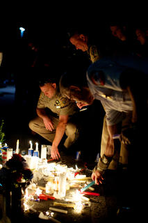 Nelson County Sheriff's Office deputies pay tribute to Bardstown Police Officer Jason Ellis during a candlelight vigil Monday night.