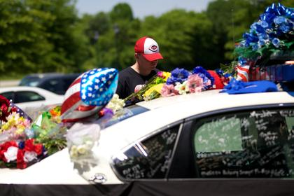 Nelson County Sheriff's Deputy Reece Riley reads some of the personal messages written on the window of a police cruiser Monday. People left tributes to Bardstown Police Officer Jason Ellis on the cruiser parked outside the police station. Ellis was murdered Saturday morning.