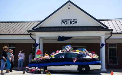 People gather at the Bardstown Police Department to pay tribute to slain Bardstown Police Officer Jason Ellis Monday.