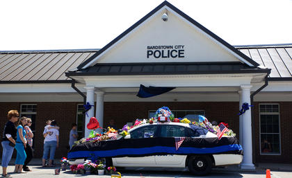People gather at the Bardstown Police Department to pay tribute to slain Officer Jason Ellis Monday.