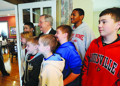 U.S. Senate Minority Leader Mitch McConnell poses Wednesday for a photo with a group of children who attended the politician's visit to My Old Kentucky Home Country Club.