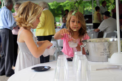 """Ten-year-old Caroline Riggs and Presley Sparks, 7, both of Bardstown, prepare cups of lemonade at Doo Dah Day Saturday in front of the J. Dan Talbott Amphitheatre. The reception before the opening of 55th season of """"The Stephen Foster Story"""" was one of many entertainment possibilities in Nelson County this weekend."""