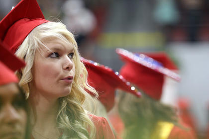 A student looks into the crowd to try to find her family.