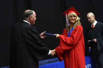 A student smiles and shakes hands with Nelson County Board  member Nicky Rapier after she receives her diploma at Nelson County High School's graduation Friday.