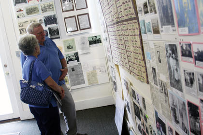 Mike Simpson and his wife, Ann, both of Bloomfield, look at photos on display in Fairfield City Hall Sunday during the Fairfield Homecoming.