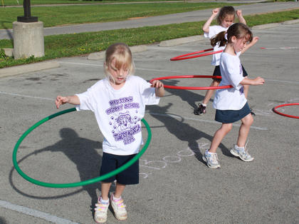 Kindergartners Lexis, left, and Abby Hatfield are twins and share their hula-hooping abilities. At back, Justice Taylor keeps up just fine.
