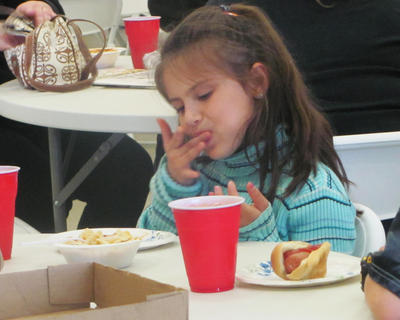 Morgan Johnson, enjoys her finger-licking good hot dog at the Harvest Homecoming chili supper held Friday, Sept. 23, at the Bishop Auction House in Bloomfield.