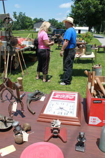 """Gary Tichnor, Fairfield, talks with Cathy Hall, who will eventually buy a tractor seat at the yard sale booth """"Old Tools and Rusty Crap"""" Tichnor sets up every year with Larry Inman, Fairfield, at the Fairfield Days and Homecoming."""