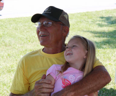 Annie Sue Lynch, 5, and her grandfather Jesse Hardin, Chaplin, enjoy conversation with a friend and the musical entertainment of Stoner Road at the 2011 Fairfield Days and Homecoming June 25.