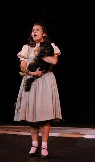 """Trish Epperson portrays Dorothy Gale as she sings """"Over the Rainbow"""" in a dress rehearsal for the 2011 production of """"The Wizard of Oz"""" as she holds a yortese named Molly, sister to Scraps, the dog portraying """"My Old Dog Trey"""" in """"The Stephen Foster Story."""""""