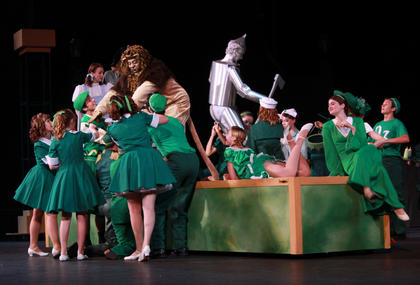 The Cowardly Lion (Aundrey Ligon) and the Tin Man (Calvin Malone) are preened by the citizens of Oz to prepare for their visit with the Wizard of Oz.