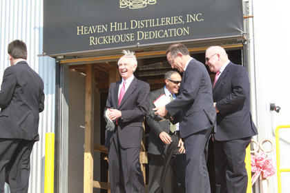 Kentucky Governor Steve Beshear and Heaven Hill President Max Shapira put on gloves before rolling the first barrel into the new rickhouse.