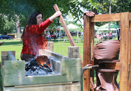 """Sandra Hall, Cox's Creek, helps her husband, blacksmith Daniel Hall, make a pair of tongs. """"I have to make all my tools before I'm able to make other things,"""" Daniel Hall said."""