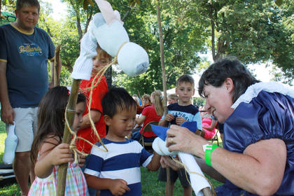 Re-enactor Bonnie Hall helps Josie and Hagan O'Daniel, both 3, make stick horses at the Wickland 19th-Century Barbecue July 9.