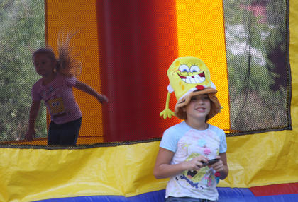 Destiny Shaw, 10, has taken a photo of her sister, Emily Metcalf, 4, jumping in the bounce house as they wait for SpongeBob SquarePants and Patrick the starfish to make an appearance at the Kentucky Railway Museum in New Haven Sunday. The sisters are from Hodgenville.