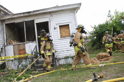 Firefighters in face masks exit the house after kindling a blaze in the kitchen — part of their orientation, in which they learned how a fire moves and spreads through a structure.