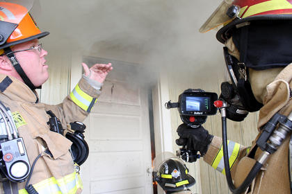 Dennis Stout uses a thermal imager to determine that temperatures are reaching 200 degrees Fahrenheit near the ceiling of a kitchen that has been set ablaze for a training exercise. Capt. Jonathan Mattingly, left, gestures toward a thermal layer of smoke that banks against a ceiling and lowers as smoke fills up a room. Stout represents Bullard, a company that makes thermal imagers.