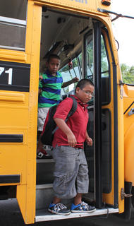 Third-grader John and fourth-grader K.C. Bradley get off the bus on the first day of the 2011-2012 school year Aug. 3.