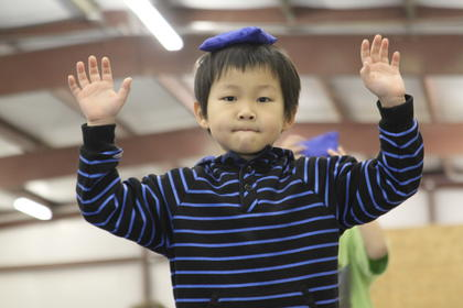 """First-grader Jin Kobayashi balances a sack on his head while walking on a balance beam at Blue Ribbon Sports on New Haven Road. Kobayashi was participating in a winter break enrichment course called """"Fitnastics,"""" which focuses on keeping kids active. The program is administered by Bardstown City Schools."""