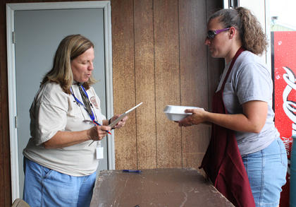 Pam Gover, one of the organizers for the first-ever Bourbon City BBQ Festival Sept. 2-3, accepts a barbecue chicken turn-in from Gretchen Lovelady of Bama Boy BBQ of Elizabethtown. Bama Boy, whose team consisted of Lovelady and husband, Josh Lovelady, took Grand Champion at the festival.