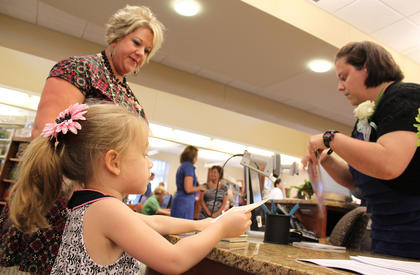 """Branch Manager Catherine Williams, right, helps Anna Ray Wheatley, 4, check out her first book at the new library, """"The Tale of Peter Rabbit."""" Mom Trista Wheatley, Lebanon, is originally from New Haven and expects to visit the new branch often. Her 6-year-old, Julia Rose, was the first person to get a library card at the branch. """"They have watched every piece of wood, every brick. They have been counting down the days,"""" Wheatley said of her daughters. """"When they found out it was the grand opening today that was all they could talk about."""""""