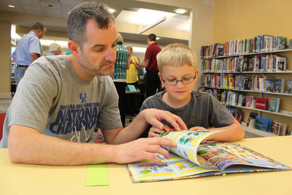 Brian Newton, Bardstown, and his 9-year-old son, Alex Newton, read in the children's section of the New Haven Branch of Nelson County Public Libraries during the branch's grand opening May 6, 2012.