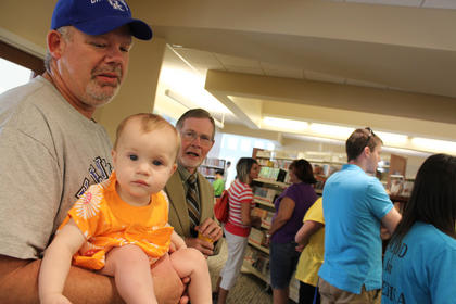 Ten-month-old Mallory Norman isn't quite ready to read yet but she still showed up with dad David Norman at the New Haven library branch grand opening May 6, 2012.