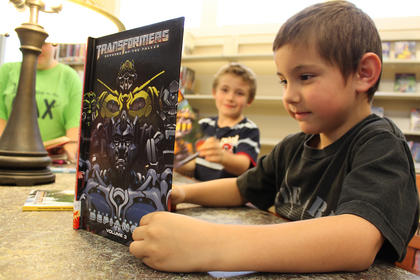 Cole Hagan, 6, reads as friend Cory Chesser, 6, looks on at the New Haven library branch May 6.