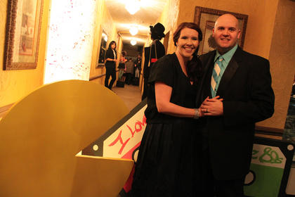 Jennifer and Johnny Warren pose with a giant Pac Man and cassette tapes at the entrance to the Beautiful Dreamer Ball.