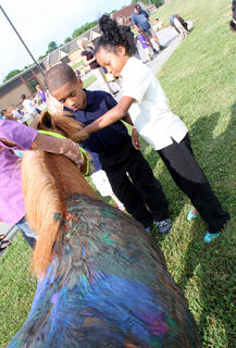 Bardstown Primary School second-graders Jeremiah Fogle, 8, and Anihya Allen, say hello to a painted miniature horse May 7. Students painted the horses to learn teamwork and other lessons.