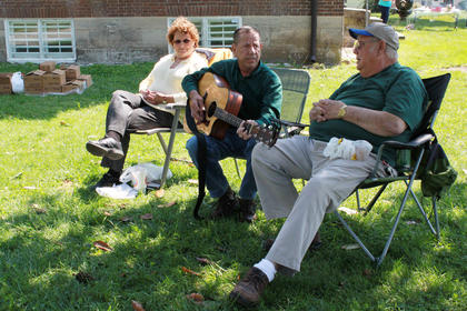 Tom Young, center, sang a song at the festival while Kathy Young and Gary Anderson listened.
