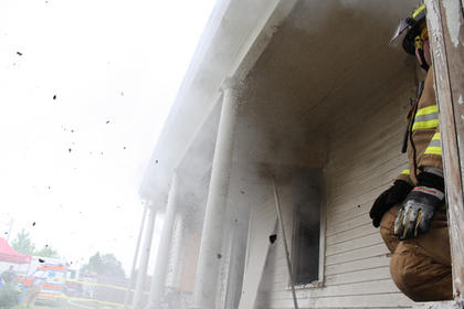 Water blasts out of a window, scattering debris as firefighter Ernie Pyle looks on.