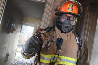 Capt. Jonathan Mattingly holds the remains of a smoke detector, often one of the first things to burn in a fire. Smoke is seen banked against the ceiling after the house aired out during a lunch break.