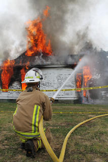 Interim Fire Chief Marlin Howard works to keep the fire under control as the house burns to the ground. Temperatures in the house exceeded 1200 degrees Fahrenheit as it burned.