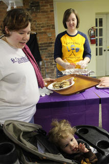 Jennifer Smith, Springfield, gets a plate of pancakes and country ham with her 21-month-old son, Soren Smith, at the St. Catherine College Pancake Breakfast Saturday morning. Daughter Midori Smith, 4, also enjoyed breakfast. Krista Rumage, Bardstown, serves out the country ham.