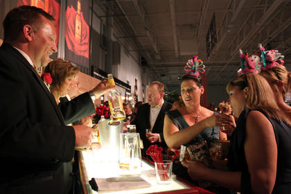 """Four Roses Director of Distillery Operations Ryan Ashley shows a bottle to Sydina Bradshaw, Bardstown, and her friends Jennifer Robinson, Wisconsin, and Carrie Hoza, Chicago, who are wearing hats to celebrate the first birthday of Makers Mark's """"46"""" bourbon."""