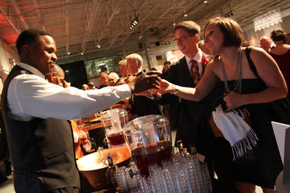 Rick Brent, Louisville, passes a Woodford Reserve to Cara and Eric Mehr, St. Paul, Minn., at the Great Kentucky Bourbon Tasting & Gala, hosted at the Guthrie Opportunity Center Saturday night.