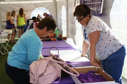 Cheryl Metcalfe, New Haven, left, signs into the survivor's booth at Relay for Life as Mary Evans, Bardstown, discusses the activities later in the day.