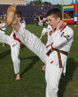 Tristan Boggs, Cox's Creek, kicks as high as he can during a karate demonstration.