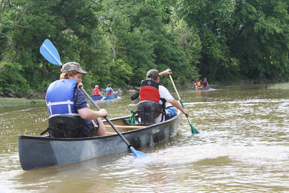 Boy Scouts paddle down Beech Fork River in search for items to pick up.