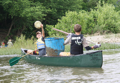 Luke Hagan showcases a Frisbee he found, as Jonah Stiles tries to maneuver the canoe.