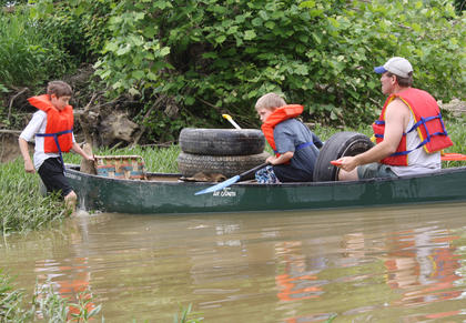 Simon Starkey, left, walks into a canoe with Blake Vittitow and Scott Starkey, after he picked up trash.