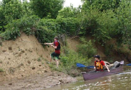 Xavier Petit, left, climbs up a hill to retrieve some trash as Elijah Rosenbaum waits in the canoe.