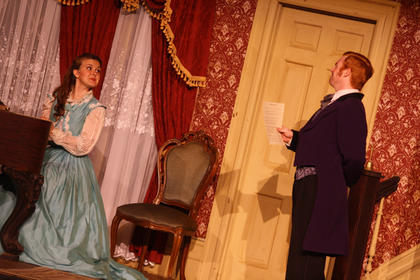 Jane McDowell (Charlotte Campbell) watches as Dudley Morton (John Michael Chappell) performs a song Stephen Foster wrote for her.