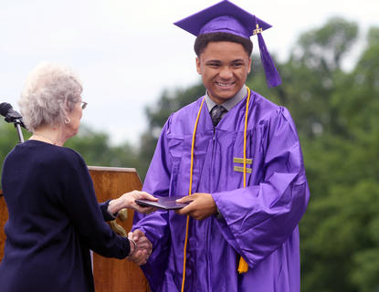 Bardstown High School graduate Jared Hickman smiles for the camera and shakes hands board member Margie Bradford after he receives his diploma Saturday.
